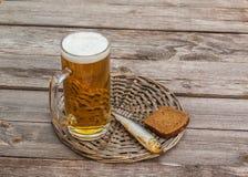 Стекло пива и копченых рыб на деревянном столе Стоковые Фотографии RF