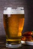 Стекло пива и крылов цыпленка на темной деревянной предпосылке стоковое фото