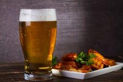 Стекло пива и крылов цыпленка на темной деревянной предпосылке стоковые фото