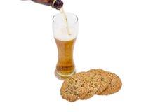 Стекло пива и смачного печенья, взбрызнутое с различными семенами Стоковое фото RF