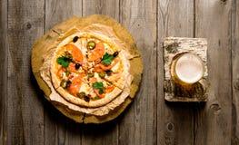 Стекло пива на стойке березы и пицце Стоковая Фотография