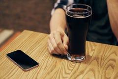 Стекло пива на таблице рядом с телефоном в баре Стоковые Изображения RF