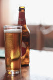 Стекло пива с бутылкой на таблице Стоковая Фотография