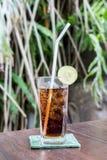 Стекло питья кокса с льдом и известкой на предпосылке природы на деревянном столе Остров Бали Стоковые Изображения