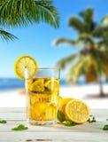 Стекло питья чая льда лета на пляже Стоковое фото RF