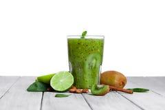 Стекло полное естественного зеленого напитка от кивиа на деревянном столе, изолированный на белой предпосылке E Стоковое Изображение