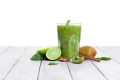 Стекло полное естественного зеленого напитка от кивиа на деревянном столе, изолированный на белой предпосылке E Стоковые Фото