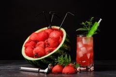 Стекло полное напитка арбуза красного с кубами и мятой льда на черной предпосылке Сочная и зрелая большая ягода с Стоковое Изображение RF