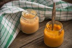 Стекло раздражает с естественным детским питанием на деревянном столе Стоковое Изображение