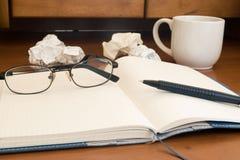 Стекло, ручка на бумаге скомканной тетрадью Стоковое фото RF