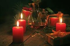 Стекло рябиновки или коньяка, подарочной коробки и свечи на деревянном столе Состав торжества Стоковое Изображение RF