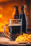 Стекло свежего пива, пива бутылки и обломоков на увольнении Стоковые Фотографии RF