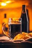 Стекло свежего пива, пива бутылки и обломоков на увольнении Стоковые Изображения