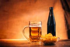 Стекло свежего светлого пива, пива бутылки и обломоков на деревянном столе Стоковые Изображения