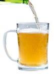Стекло светлого пива лить от бутылки на белой предпосылке Стоковые Изображения RF