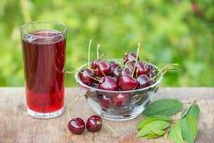 Стекло сока вишни и шара вишен на таблице в саде outdoors Стоковое Изображение