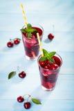 Стекло сока вишни на голубой таблице Стоковое Изображение