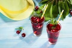 Стекло сока вишни на голубой таблице Стоковое Фото