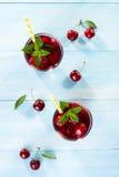 Стекло сока вишни на голубой таблице Стоковые Фото