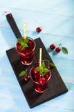 Стекло сока вишни на голубой таблице Стоковые Фотографии RF