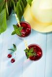 Стекло сока вишни на голубом деревянном столе Стоковые Фото
