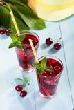 Стекло сока вишни на сини таблица Стоковое Изображение