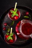 Стекло сока вишни на черном подносе Стоковые Фотографии RF