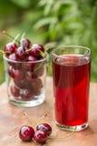 Стекло сока и вишен вишни на таблице outdoors Стоковое фото RF