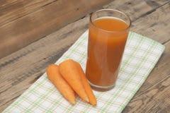 Стекло сока моркови и зрелых морковей Стоковые Изображения