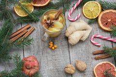 стекло состава рождества bauble голубое Елевые ветви, тросточка конфеты, грея чай с имбирем и лимон Стоковые Фото