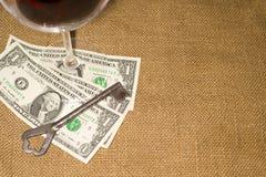 Стекло, старые банкнот ключевых и немного долларов США на старой ткани Стоковое Изображение