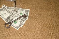 Стекло, старые банкнот ключевых и немного долларов США на старой ткани Стоковое Изображение RF
