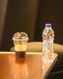 Стекло холодного кофе и бутылки воды на таблице Стоковое Фото