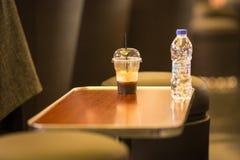 Стекло холодного кофе и бутылки воды на таблице Стоковые Фото