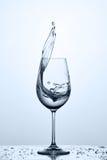 Стекло холодного уборщика брызгая воду пока стоять на стекле с водой клокочет против светлой предпосылки стоковая фотография