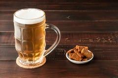 Стекло холодных пенистых пива лагера и плиты закусок на деревянных животиках Стоковые Изображения RF
