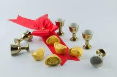 Стекло чая кувшина золота смычка ленты золотого ингота красное на белой предпосылке Стоковое Фото