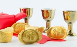 Стекло чая кувшина золота смычка ленты золотого ингота красное на белой предпосылке Стоковая Фотография RF