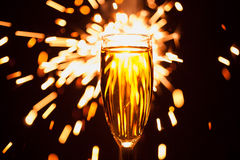 Стекло Шампани против предпосылки бенгальского огня Стоковое Изображение RF