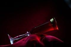 Стекло шампанского на красном бархате на низком конце ключа вверх Стоковое Изображение