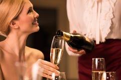 Стекло шампанского официантки заполняя Стоковое фото RF