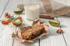 Стекло югурта, handmade бара granola, свежих фруктов и гаек на белой деревянной поверхности Стоковые Фотографии RF