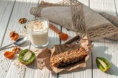 Стекло югурта, handmade бара granola, свежих фруктов и гаек на белой деревянной поверхности Стоковые Фото