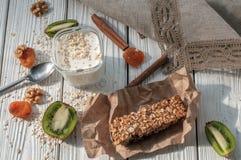Стекло югурта, handmade бара granola, свежих фруктов и гаек на белой деревянной поверхности Стоковое Изображение