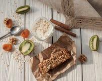 Стекло югурта, handmade бара granola, свежих фруктов и гаек на белой деревянной поверхности Стоковое фото RF