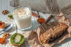 Стекло югурта, handmade бара granola, свежих фруктов и гаек на белой деревянной поверхности Стоковая Фотография RF