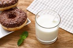 Стекло donuts молока и шоколада на деревянном столе Стоковое Фото