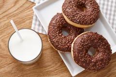 Стекло donuts молока и шоколада на деревянном столе Стоковые Фотографии RF