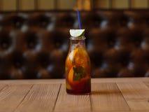 Стеклянная бутылка с освежая холодным напитком, куском душистой известки на запачканной деревянной предпосылке Стоковое Фото