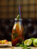 Стеклянная бутылка с освежая холодным напитком, куском душистой известки с плитой изюминок на запачканной предпосылке Стоковые Фотографии RF